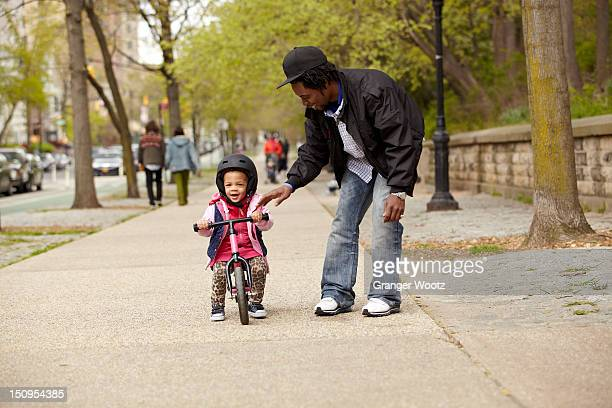 Father helping daughter ride bicycle on sidewalk