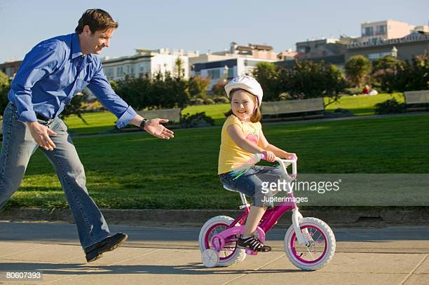 Father helping daughter ride with training wheels