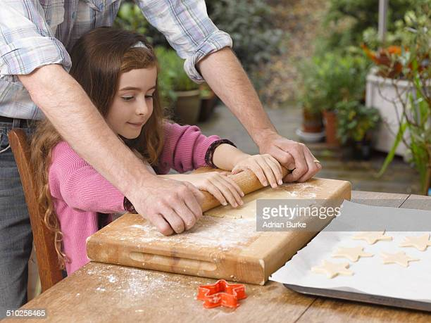 Father helping daughter rolling out biscuit dough