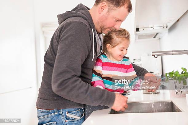 Father helping daughter to wash her hands