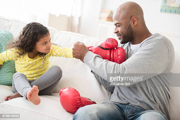 Father helping daughter with boxing gloves