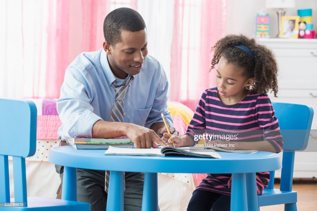 Father helping daughter with homework in playroom : Foto stock