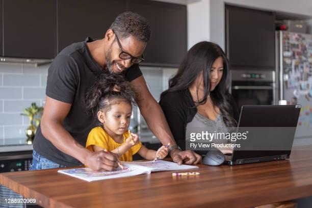 vader die dochter met schoolopdracht helpt terwijl de vrouw op laptopcomputer werkt - onschuld stockfoto's en -beelden