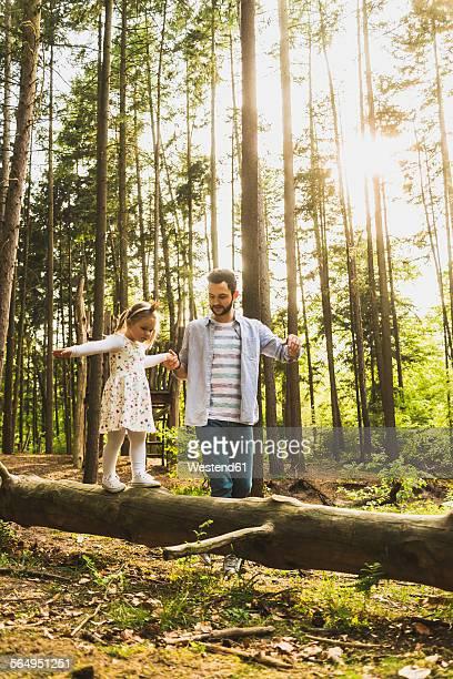 Father helping girl balancing on log