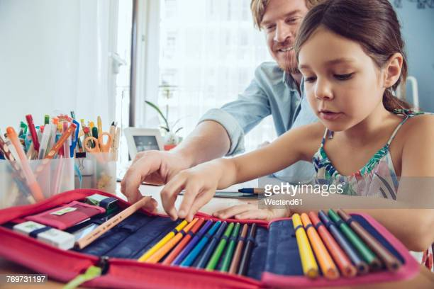 Father helping girl doing her schoolwork at home