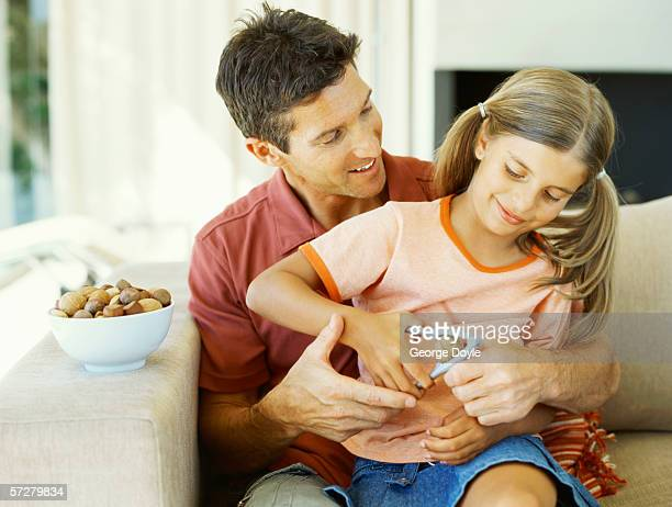Father helping her daughter to break a walnut