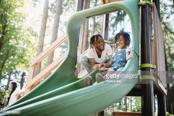 father helping his child on playground slide - tacoma stock pictures, royalty-free photos & images