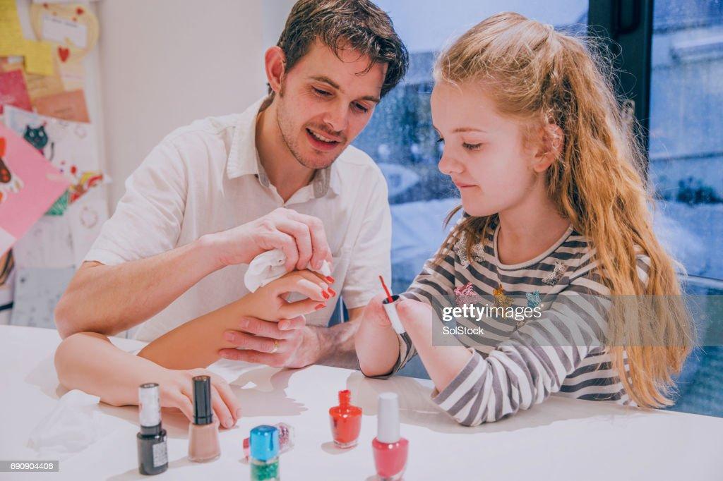 Pai, ajudando sua filha tinta seu membro protético Nails : Foto de stock
