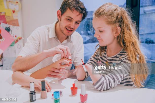 father helping his daughter paint her prosthetic limb nails - paraplegic stock photos and pictures