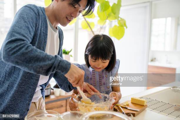 Father helping his daughter to bake