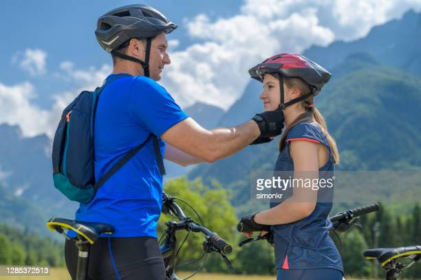 father helping his daughter to wear a helmet - fingerless gloves stock pictures, royalty-free photos & images