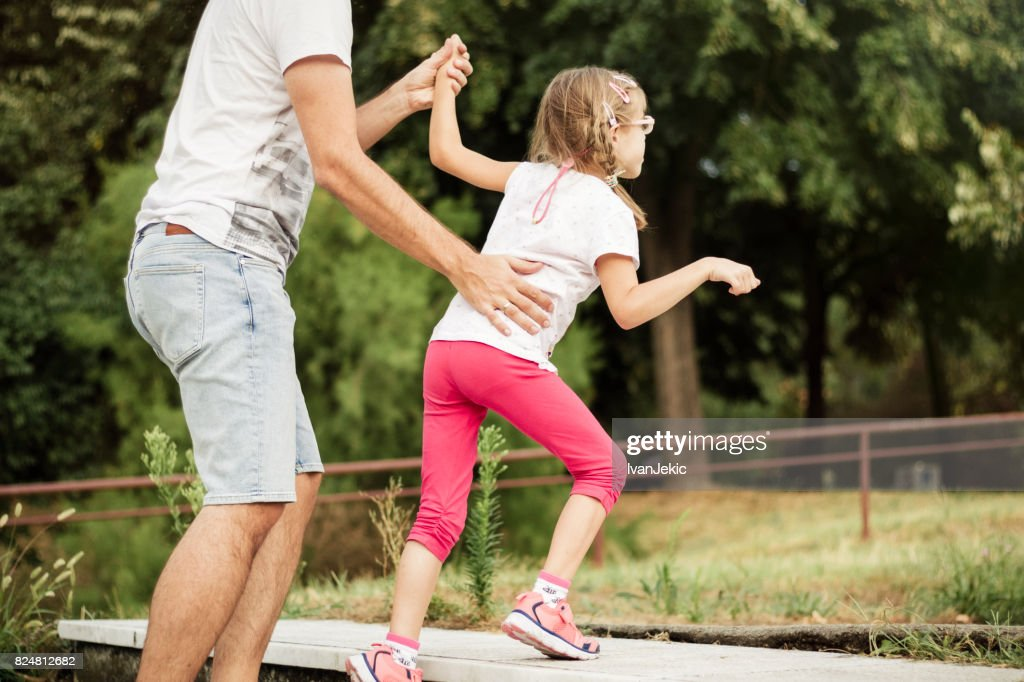 Father helping his daughter with a mild CP to walk up the stairs : Stock Photo