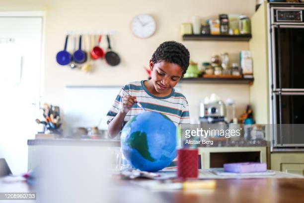 father helping his son make a globe in his kitchen at home - homeschool stock pictures, royalty-free photos & images