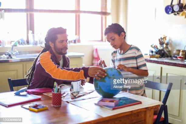 father helping his son make a globe in his kitchen - art and craft stock pictures, royalty-free photos & images