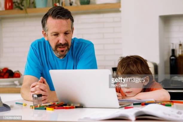a father helping his son with homeschooling. - learning disability stock pictures, royalty-free photos & images