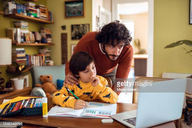 father helping his son with schoolwork - education stock pictures, royalty-free photos & images