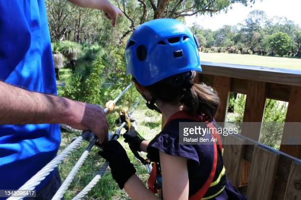 father helping his young daughter to ride on a zip line in a forest - rafael ben ari - fotografias e filmes do acervo