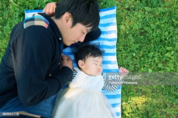 father helping infant girl ( 6-11 months )  crawl at park under sunshine - 6 11 months stock pictures, royalty-free photos & images