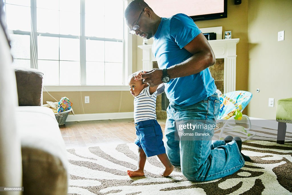 Father helping infant son learn to walk in home : Stock Photo