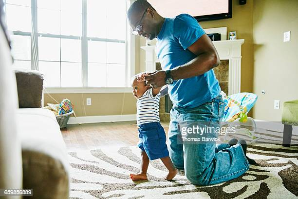 Father helping infant son learn to walk in home