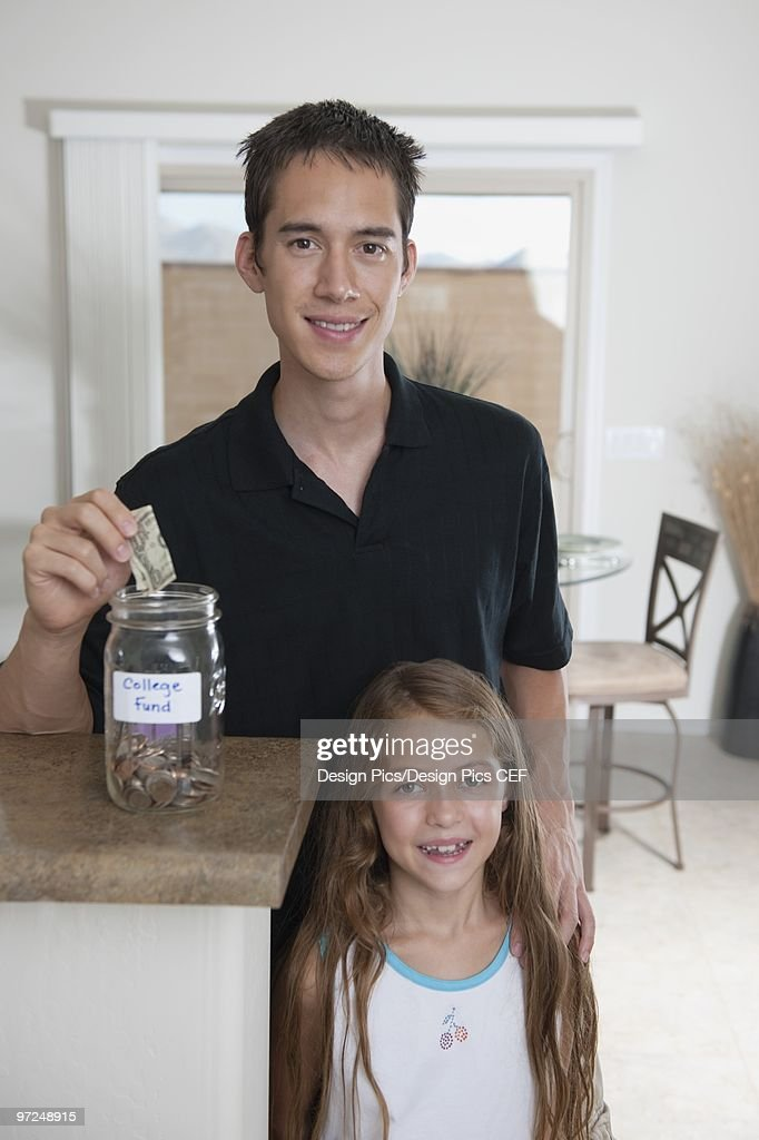 A father helping is daughter save for college : Stock Photo