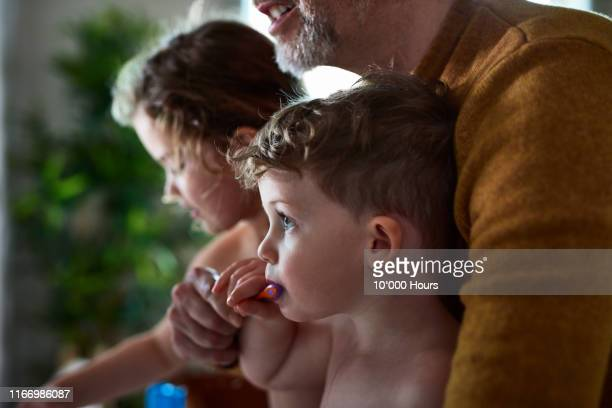 father helping little boy to brush his teeth - preparation stock pictures, royalty-free photos & images