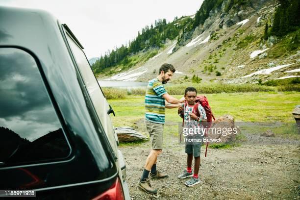 Father helping son adjust backpack before beginning camping trip