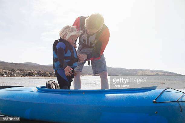 Father helping son adjust lifejacket in canoe, Loch Eishort, Isle of Skye, Hebrides, Scotland