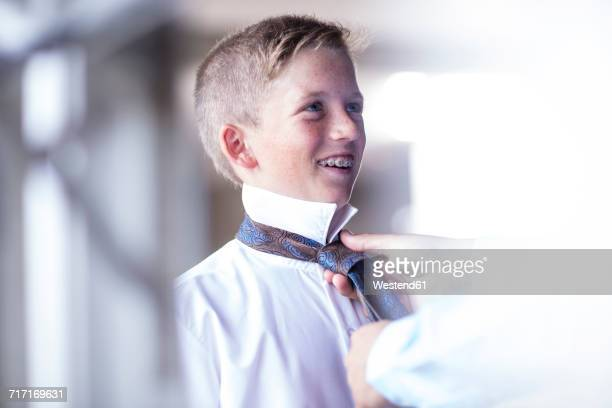 Father helping son binding his tie