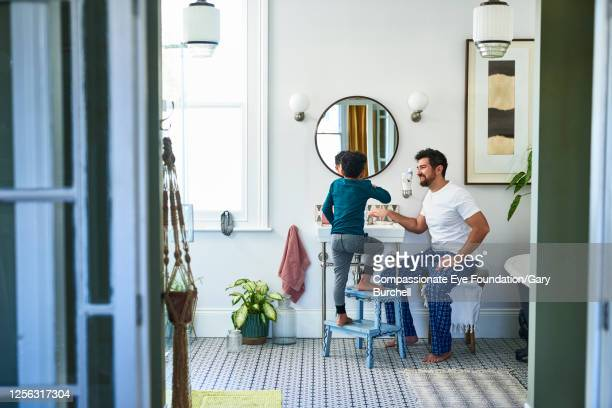 father helping son brushing teeth in bathroom - toilet planter stock pictures, royalty-free photos & images