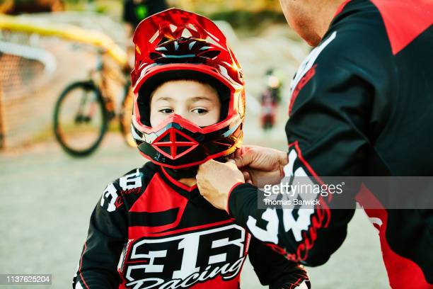 Father helping son buckle up helmet before BMX race