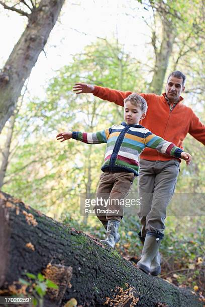 Father helping son cross log outdoors