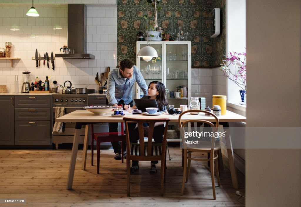Father helping son in doing homework at home : Stock Photo
