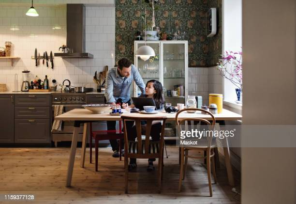 father helping son in doing homework at home - people icons stock pictures, royalty-free photos & images