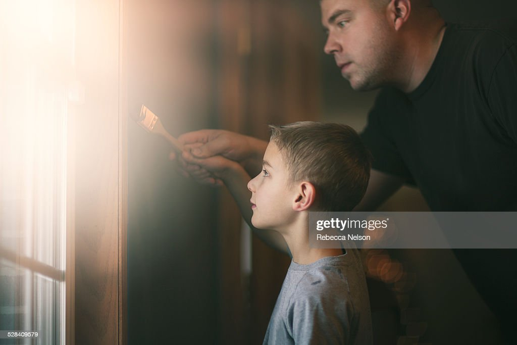 father helping son paint : Stock Photo