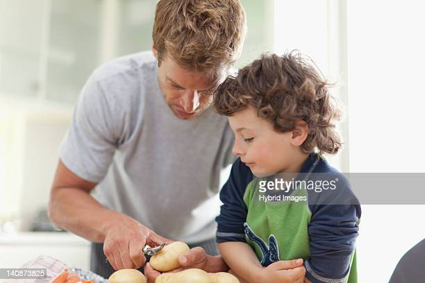 Father helping son peel potatoes