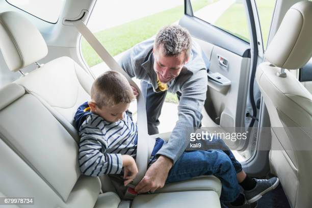 father helping son put on seat belt in car - family inside car stock photos and pictures