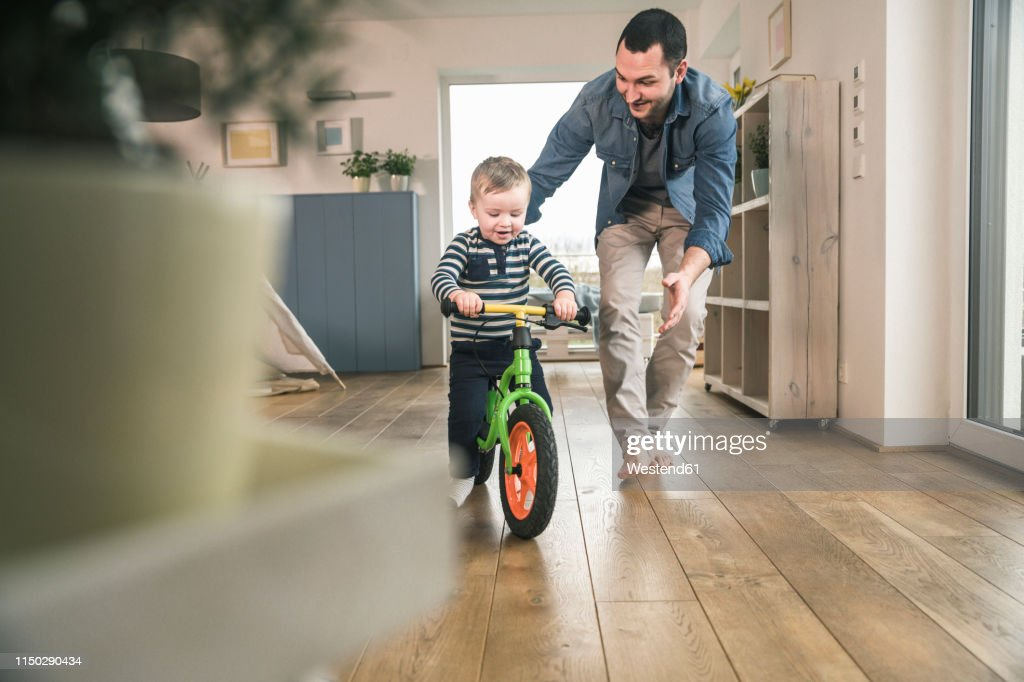 Father helping son riding with a balance bicycle at home : Stock-Foto