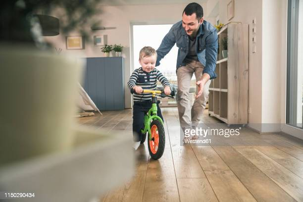 father helping son riding with a balance bicycle at home - vater stock-fotos und bilder
