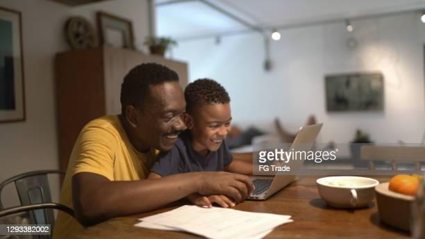father helping son studying at home - mindzoom 2 stock pictures, royalty-free photos & images