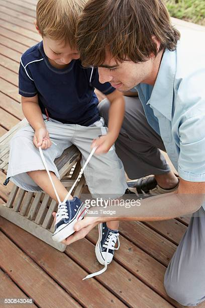Father helping son tie shoelaces
