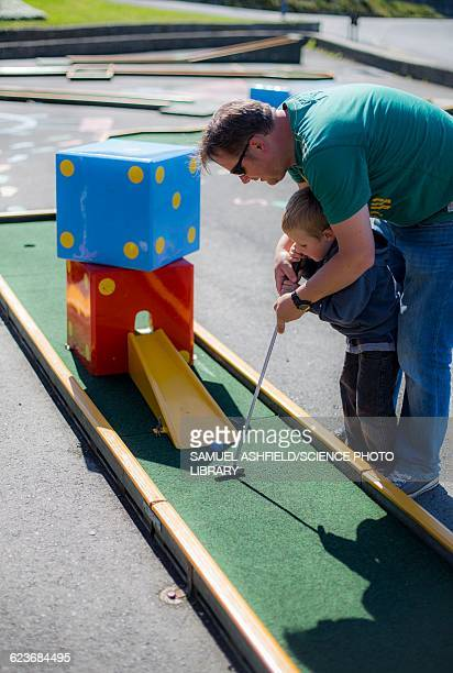 Father helping son to play mini golf