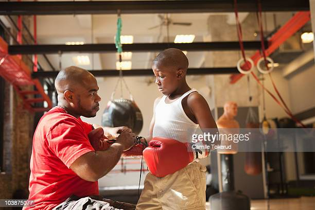 Father helping son to put boxing gloves on