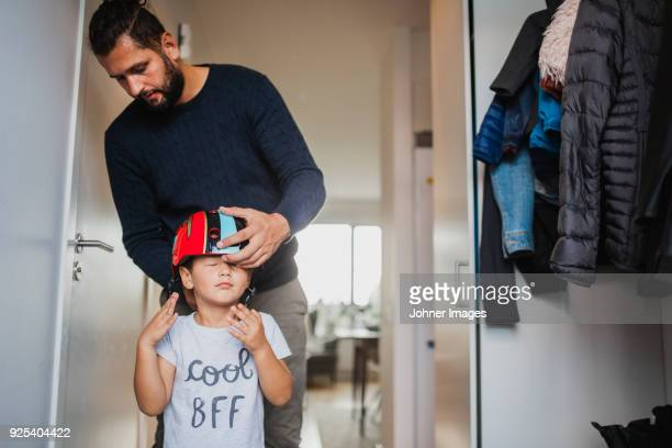 father helping son to put on cycling helmet - sportschutzhelm stock-fotos und bilder