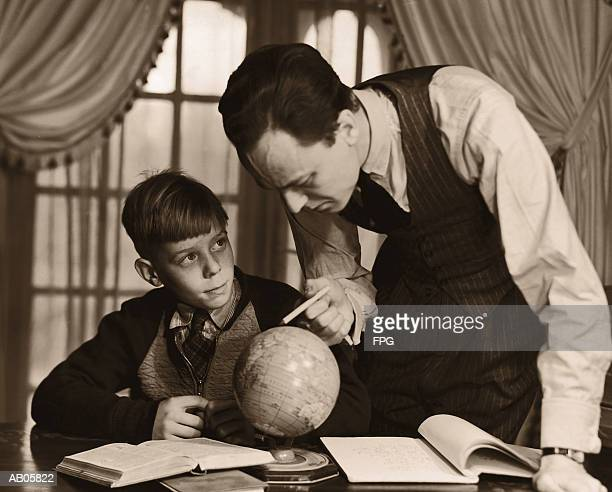 father helping son (10-12) with geography homework (b&w sepia tone) - 20th century stock pictures, royalty-free photos & images