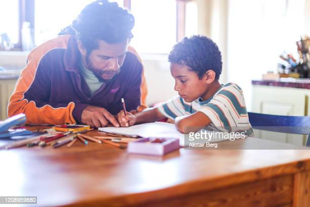 father helping son with his homework at home - parenting stock pictures, royalty-free photos & images