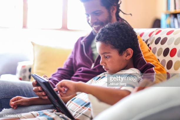 father helping son with his homework on a tablet computer - genderblend stock pictures, royalty-free photos & images