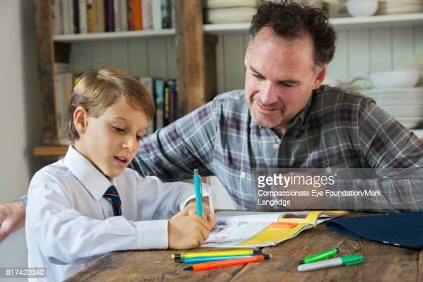 Father helping son with homework at kitchen table