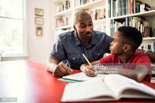 father helping son with homework - hausaufgabe stock-fotos und bilder