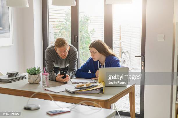 father helping teenage daughter with revision - demonstration stock pictures, royalty-free photos & images